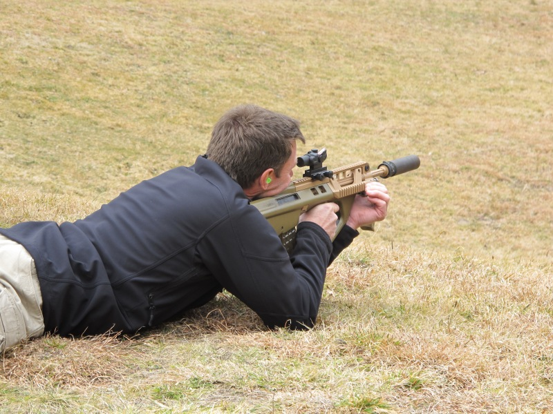 "Rob Maylor, a former SASR sniper, firing the 16"" barrel EF88 (fitted with Ase Utra suppressor, Trijicon TA44SR-10 1.5x16 ACOG, and folding foregrip)"